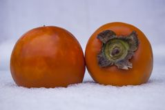Two ripe orange persimmons lie in the snow Royalty Free Stock Image