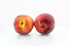 Two ripe peaches in the water droplets on white background Royalty Free Stock Photography