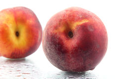Two ripe peaches in the water droplets on white background Royalty Free Stock Photo
