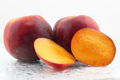 Two ripe peaches in the water droplets on white background Royalty Free Stock Image