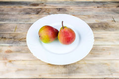 Two ripe pears in white plate on rustic wooden table Stock Photos