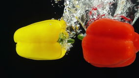 Two Ripe Peppers Falling Through Water. stock video footage