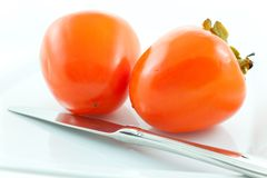 Two ripe persimmons and steel knife Royalty Free Stock Photo