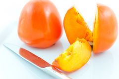 Two ripe persimmons and steel knife Royalty Free Stock Image