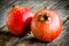 Two ripe pomegranate on a wooden background Royalty Free Stock Photo