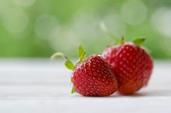 Two strawberries on a wooden table Royalty Free Stock Photos