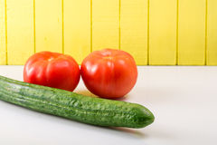Two ripe tomatoes and cucumber on a light background propped Royalty Free Stock Photos