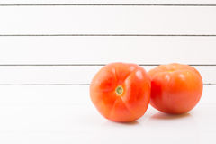 Two ripe tomatoes on a light background propped up Royalty Free Stock Photo