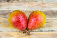 Two ripe yellow and red pears on rustic wooden background Stock Image