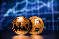 Two ripple coins with financial charts on background. Two ripple coins with chart background. Ripple or XRP is one of top cryptocurrencies royalty free stock photo