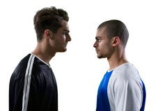 Two rival football player looking at each other. Against white background Stock Images