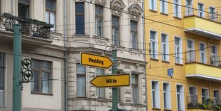 Two road signs with the arrow and the indications of the most im. Two yellow road signs with the arrow and the indications of the most important districts of stock photo