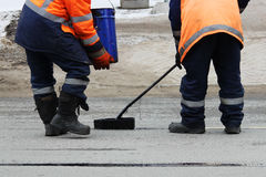 Two road workers in overalls are poured with hot tar on the edge of the road strip when repairing the road Royalty Free Stock Photography