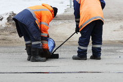 Two road workers in overalls are poured with hot tar on the edge of the road strip when repairing the road Stock Images