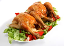 Two roast chickens on a bed of salad Royalty Free Stock Photography