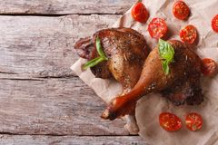 Two roasted duck legs with basil and tomatoes closeup  an table Stock Photos