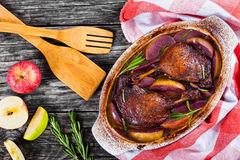 Two roasted duck legs grilled in red wine and apple stock images