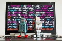Robots with source code screen, artificial intelligence, deep learning concept. Two robots looking at laptop screen with source code, artificial intelligence royalty free stock image