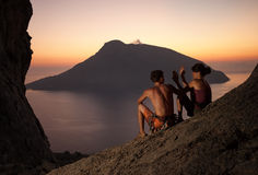 Two rock climbers having rest at sunset. Climbers giving high five and cheering. With picturesque view of Telendos Island in front. Kalymnos Island, Greece Royalty Free Stock Photos