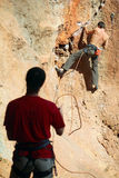 Two rock climbers, one belaying Royalty Free Stock Photography