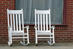 Two Rockers. Two empty white rocking chairs on city street Stock Images
