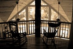 Two rocking chairs in sepia. Two antique chairs sitting on a balcony at the railing inside a house. Hickory flooring and pecky cypress ceilings royalty free stock photos