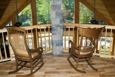 Two rocking chairs w/view. Two antique chairs sitting on a balcony at the railing inside a house. Hickory flooring and pecky cypress ceilings stock images