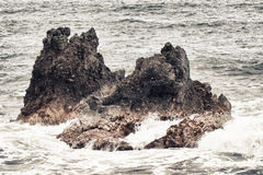 Two rocks in the ocean during storm Royalty Free Stock Photo
