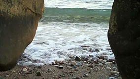 Two rocks and sea in between. Waves are breaking between two rocks on the coast stock video
