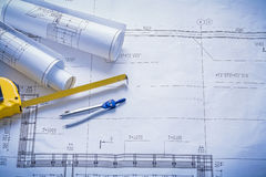 Two rolled blueprints tapeline compass with Royalty Free Stock Photo