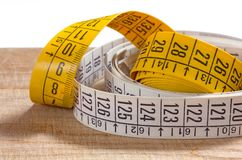 Two Tailor Measuring Tapes on a Wooden Surface. Two rolled-up white and yellow tailor measuring tapes on an old wooden surface Royalty Free Stock Images