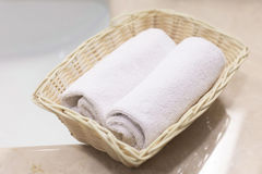 Two rolled white hand towels in light rectangular basket on the Stock Photography