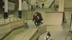 Two roller skaters slide on fence with cross legs. Springboard. Extreme. Competition in skatepark. Slow motion stock video