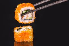 Two Rolls Calivornia and shelves. For Japanese food on a black background Stock Image