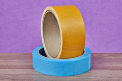 Two rolls of duct tape lying on table, lilac background. One roll of yellow double-sided tape and one roll masking tape blue lie on a table on a purple Royalty Free Stock Photos