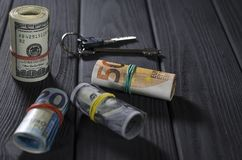 Two rolls of hundred-dollar bills, a fifty-roll roll, a twenty-euro roll tied with rubber bands on a black wooden table stock photo