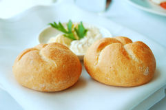 Two rolls on a white plate. Served with garlic butter Royalty Free Stock Photos