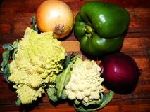 Two Romanescu cabbage, yellow onion, purple onion, green bell pepper Stock Photo
