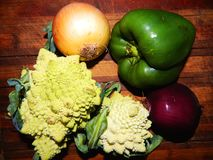 Two Romanescu cabbage, yellow onion, purple onion, green bell pepper Royalty Free Stock Image