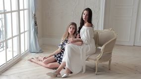 Two romantic fashion models posing sitting on chair in beaytiful interior stock footage