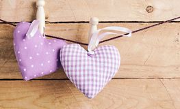 Two romantic purple hearts pegged on a line. One polka dot and one checked, tied with wooden pegs over a rustic wood background with copy space royalty free stock image