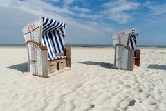 Two roofed wicker beach chairs at the coastline of the German island Norderney in front of the ocean. Wide angle view stock photos