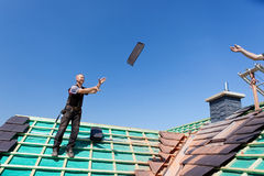 Two roofers tossing tiles Royalty Free Stock Photo