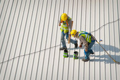 Two rooftop workers. Two construction workers, wearing safety harness and secured with rope and carabiner, working on metal rooftop with paint cans nearby stock photos