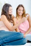Two roommates checking smart-phone Royalty Free Stock Images
