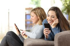 Two roommates using multiple devices at home. Two roommates using multiple devices sitting on a couch in the living room at home Stock Photo