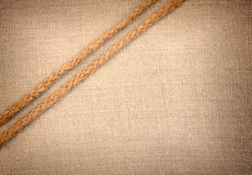 Two ropes going diagonally  on fabric  background Royalty Free Stock Image