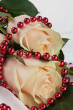 Two roses with red beads on a white cloth Royalty Free Stock Photos