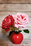 Two roses in red vase on aged wooden background Royalty Free Stock Images