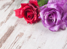 Two roses on wooden background Stock Images